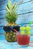 Le fruit d'ananas avec les lunettes de soleil bleues boit le cocktail fruité Photo libre de droits