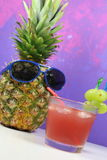 Le fruit d'ananas avec les lunettes de soleil bleues boit le cocktail fruité Image stock