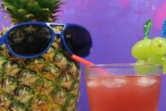 Le fruit d'ananas avec les lunettes de soleil bleues boit le cocktail fruité Image libre de droits