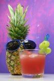 Le fruit d'ananas avec les lunettes de soleil bleues boit le cocktail fruité Images stock