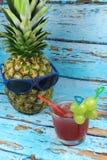 Le fruit d'ananas avec les lunettes de soleil bleues boit le cocktail fruité Photos stock