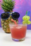 Le fruit d'ananas avec les lunettes de soleil bleues boit le cocktail fruité Photographie stock libre de droits
