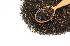 Le fruit fleurit le thé noir de pétales dans la cuillère d'isolement sur le backgr blanc Image stock