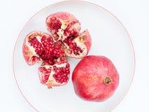 Le fruit mûr de grenade d'un plat blanc de porcelaine Photographie stock libre de droits