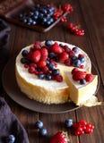 Le gâteau au fromage crémeux fait maison de mascarpone avec la forêt de baies porte des fruits et des fraises sur la table en boi images stock