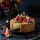 Le gâteau au fromage a servi avec les figues, les écrous et le miel frais Images stock