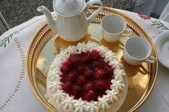 Le gâteau avec la fraise et la crème attend pour être servi ainsi qu'une tasse de café fort Image stock
