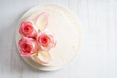 Le gâteau blanc doux de buttercream avec la rose de rose fleurit sur le dessus Photos libres de droits