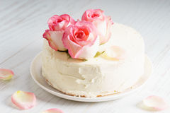 Le gâteau blanc doux de buttercream avec la rose de rose fleurit sur le dessus Photo stock