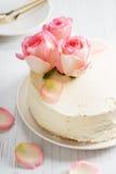 Le gâteau blanc doux de buttercream avec la rose de rose fleurit sur le dessus Photographie stock