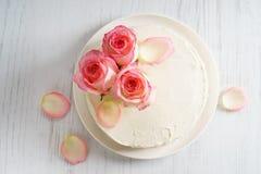 Le gâteau blanc doux de buttercream avec la rose de rose fleurit sur le dessus Photo libre de droits