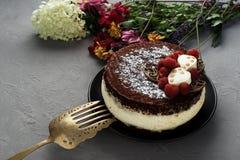 Le gâteau couvert du chocolat a décoré des framboises, avec un bouquet des fleurs sur un fond gris Photographie stock libre de droits
