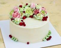 Le gâteau d'anniversaire avec des fleurs s'est levé sur le fond clair Photographie stock libre de droits