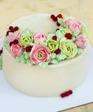 Le gâteau d'anniversaire avec des fleurs s'est levé sur le fond clair Photographie stock