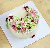 Le gâteau d'anniversaire avec des fleurs s'est levé sur le fond clair Photo stock
