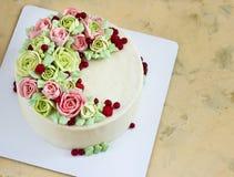 Le gâteau d'anniversaire avec des fleurs s'est levé sur le fond clair Photos stock