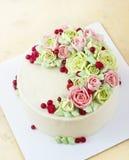 Le gâteau d'anniversaire avec des fleurs s'est levé sur le fond clair Image libre de droits