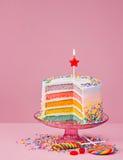 Le gâteau d'anniversaire d'arc-en-ciel avec arrose Image libre de droits