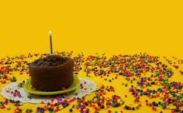 Le gâteau d'anniversaire de chocolat avec 1 bougie bleue et blanche s'est allumé, d'un petit plat vert, entouré par des boules de Photo libre de droits