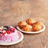 Le gâteau d'anniversaire et les petits pains avec la salutation en bois se connectent le fond rustique En bois chantez avec le jo Photographie stock libre de droits