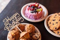 Le gâteau d'anniversaire et les petits pains avec la salutation en bois se connectent le fond rustique En bois chantez avec le jo Photo stock