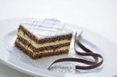 Le gâteau de chocolat avec de la crème et le chocolat tourbillonne du plat blanc, dessert doux, la pâtisserie, photographie pour  Photographie stock