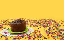 Le gâteau de chocolat d'un petit plat vert, entouré par des boules de sucrerie a dispersé sur un fond jaune Image avec l'espace d Image stock