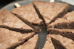 Le gâteau de chocolat a servi dans les morceaux d'un plat noir Images stock