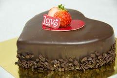 Le gâteau de coeur de chocolat orthographie l'amour Images stock