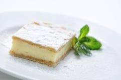 Le gâteau de crème de vanille avec la poudre de sucre et la menthe poussent des feuilles du plat blanc, du dessert doux ou du pet Image libre de droits