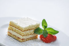 Le gâteau de crème de vanille avec la poudre de sucre, la fraise et la menthe poussent des feuilles du plat blanc, du dessert dou Images stock