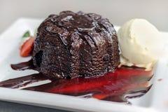 Le gâteau de lave avec la crème glacée et la fraise sauce Photo stock