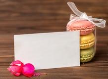 Le gâteau de Macarons a attaché le ruban, la fleur fuchsia rouge et le blanc vide, Photographie stock