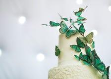 Le gâteau de mariage à deux étages est décoré des papillons verts photo libre de droits