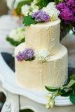 Le gâteau de mariage à multiniveaux avec le lilas sur la table Images stock