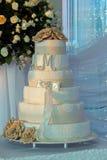 Le gâteau de mariage blanc de niveau multi sur une base et un or argentés fleurit Image libre de droits