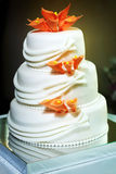 Le gâteau de mariage de niveau multi blanc avec les lis oranges fleurissent des décorations Photos libres de droits