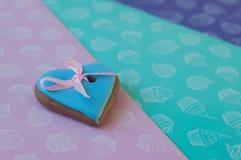 Le gâteau de miel vitré en forme de coeur avec le ruban rose s'est trouvé sur le fond coloré Photographie stock