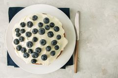 Le gâteau de myrtille de crème sure a servi d'un plat sur un CCB blanc de pierre Photographie stock libre de droits