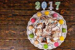 Le gâteau de nouvelle année avec un bon nombre de bougies et les macarons s'approchent des bougies numériques Photographie stock libre de droits