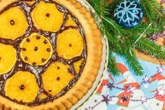Le gâteau du ` s de nouvelle année avec des oranges et le sapin s'embranchent avec le décor de Noël Photographie stock libre de droits