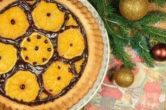 Le gâteau du ` s de nouvelle année avec des oranges et le sapin s'embranchent avec le décor de Noël Image libre de droits