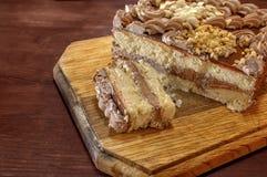 Le gâteau est coupé sur un conseil en bois Photo stock