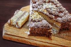 Le gâteau est coupé sur un conseil en bois Photos libres de droits