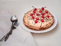 Le gâteau fait maison avec de la crème d'aigre-chocolat et chocolat arrose et les cerises de cocktail, la serviette blanche et le photographie stock