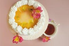 Le gâteau fait maison avec la gelée jaune a décoré le creamcup blanc sur la table rose Vue supérieure Tasse de thé le fond brouil Photos libres de droits