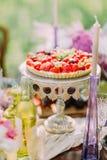 Le gâteau mousseline de fruit de mariage est décoré des fraises et des cerises Il est placé sur le gâteau de conseil entouré Images libres de droits