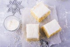 Le gâteau mousseline frais fait maison dans la crème de noix de coco et les flocons sur le festin ont servi dans les parties un f Photo stock