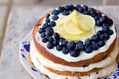 Le gâteau nu de myrtille de citron avec des myrtilles sur le dessus et le mascarpone beurrent le givrage Image libre de droits