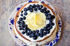Le gâteau nu de myrtille de citron avec des myrtilles sur le dessus et le mascarpone beurrent le givrage Images stock